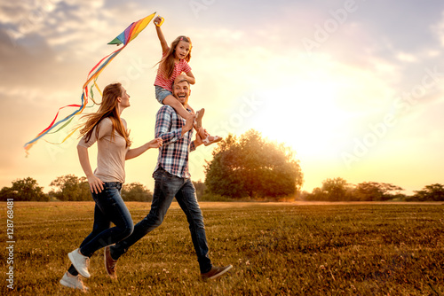 Photographie  familie mit tochter rennt und lässt drachen steigen