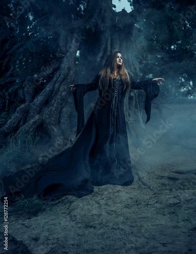 Fototapeta Dark witch casts a spell. In the background, mystical atmosphere. Photoshoot fantasy. Model big, beautiful woman. Unusual, gloomy, gothic decorations. obraz na płótnie