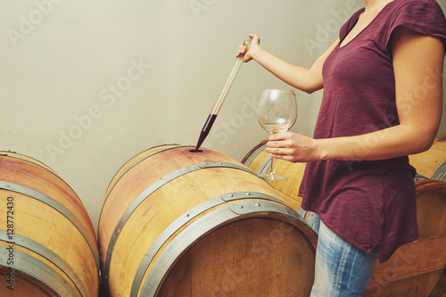 Fotografía  Winemaker getting sample of red wine from barrel.