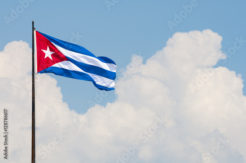 Cuban flag flying from a flagpole in the wind in front of a soft blue sky with t Wallpaper Mural