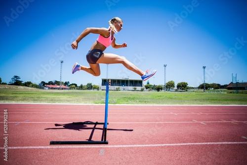 Cuadros en Lienzo Female athlete jumping above the hurdle