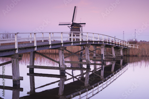 Netherlands, Kinderdijk, Traditional Dutch windmills and bridge, dusk Plakat