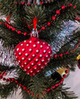 Closeup of red heart hanging from a decorated Christmas tree.