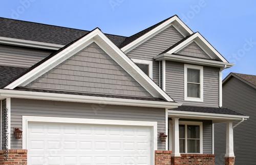 Fényképezés  New home with vinyl siding, gutters, roof
