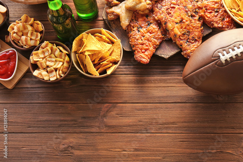 Fotografia, Obraz  Tasty snacks and rugby ball on wooden table