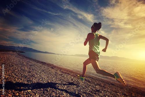 healthy lifestyle young woman runner running on sunrise seaside Fototapet
