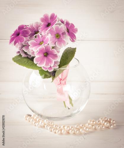Foto op Plexiglas Magnolia Bouquet of primroses in round vase and women's pearl necklace