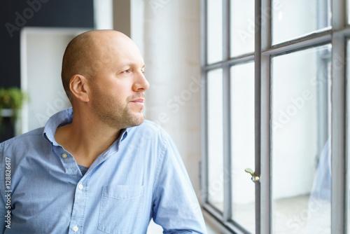 Photo mann schaut nachdenklich aus dem fenster