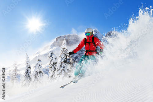 Freeride skier on piste running downhill Fototapeta