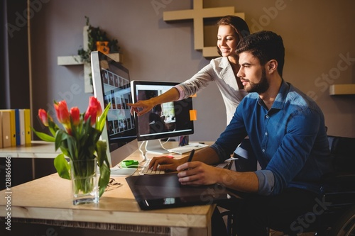 Woman showing her colleague something on the screen