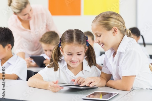 School kids using digital tablet in classroom