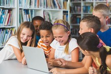 Smiling School Kids Looking At Laptop In Library