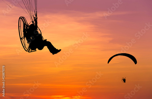 paragliders flying with paramotor on sunset