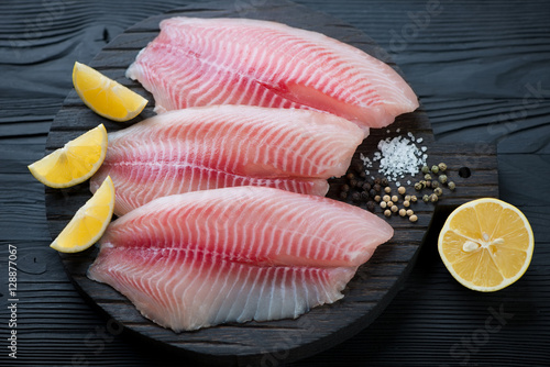 Black wooden chopping board with raw fresh tilapia fillets Wallpaper Mural