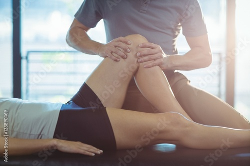 Carta da parati Physiotherapist giving knee therapy to a woman