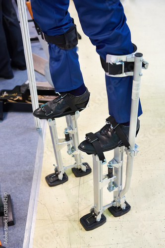 Fotografia, Obraz  Workers stilts wearing on legs of men