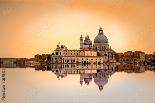 Fényképezés  Isolated Basilica di Santa Maria della Salute at orange colors reflected on the water surface, Venice, Italy