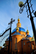 Beautiful Orthodox Church Of Red Brick With A Blue Roof, With Golden Domes At Sunset. Russia, Belgorod. General Appearance. Vertical Orientation