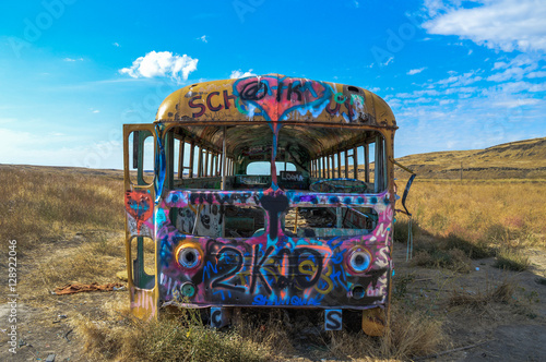Photo  Front of school bus with lots of graffiti.