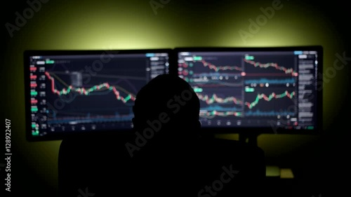 Stockbroker is Working on the Financial Market in a Dark Monitoring Room With Display Screens