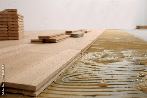 Obraz Construction in a renovated room installation of parquet.Pad applied with glue for parquet - fototapety do salonu