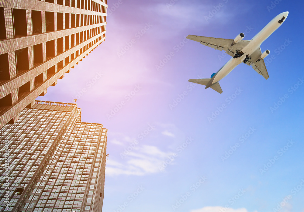 Photo  Modern tower with airplane flying over city