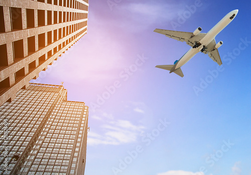 Foto  Modern tower with airplane flying over city