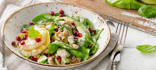 Salad with chicken, orange, spinach and pomegranate seeds.