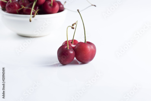 red cherries laid on a clear foreground and background cherries in a bowl.