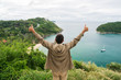 Victory and delight. A young man raising his hands up against the sky, and on the sea landscape. Thumbs up.