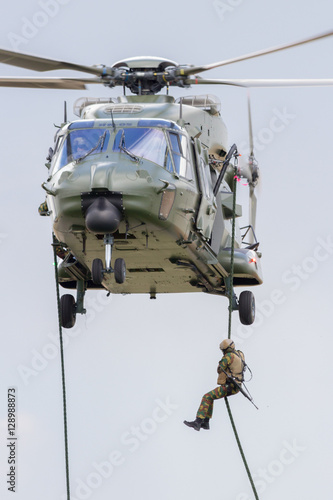 Tuinposter Helicopter Soldier fast-roping from a helicopter