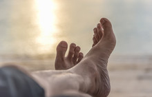 Feet Of Male On The Beach, Sunset Background