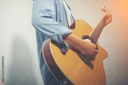 Fotografija  Young woman playing a guitar