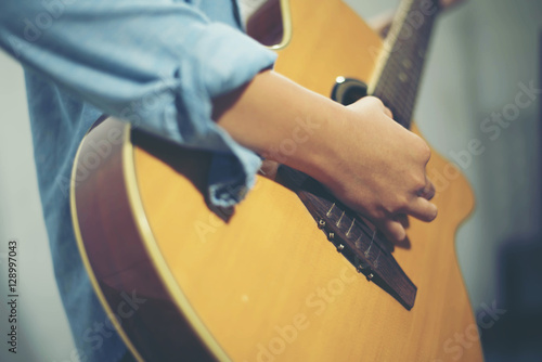 Fotografering  Young woman playing a guitar