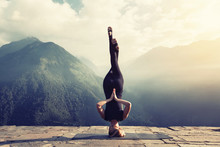 Young Woman Doing Complex Yoga Exercise Headstand With Namaste Asana. Amazing Yoga Landscape In Beautiful Mountains