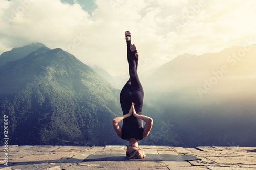 In de dag School de yoga Young woman doing complex Yoga exercise headstand with Namaste asana. Amazing Yoga landscape in beautiful mountains