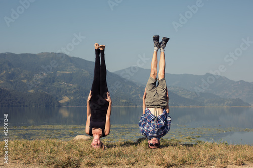 Valokuvatapetti Couple of young yogis stand on his head while doing yoga headstand asana