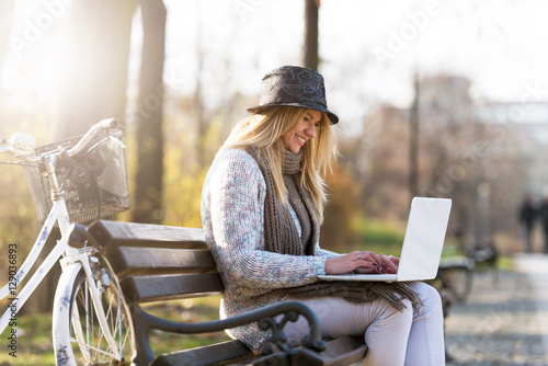 Deurstickers Blonde student girl with hat on park bench working on laptop