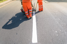 Thermoplastic Spray Marking Machine During Road Construction. Worker Painting White Line On The Street Surface (Road Worker Painting)