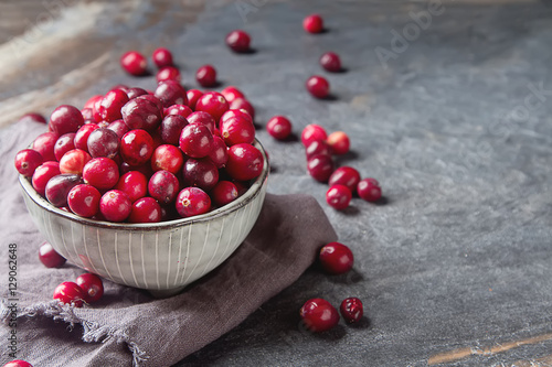 Fotografia  Red berries on a dark background. cranberries in a bowl.