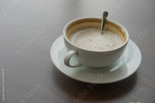 Wall Murals Cafe hot coffee in white cup white foam with silver spoon on wooden table at coffee time sunset / hot coffee