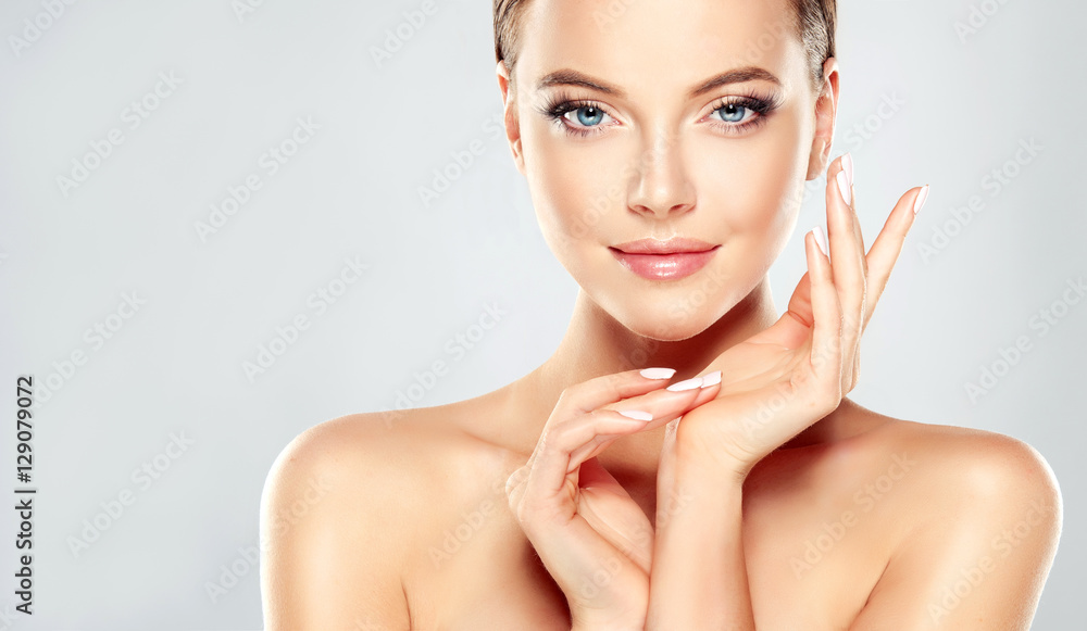 Fototapeta Beautiful Young Woman with Clean Fresh Skin touch own face . Facial treatment . Cosmetology , beauty and spa