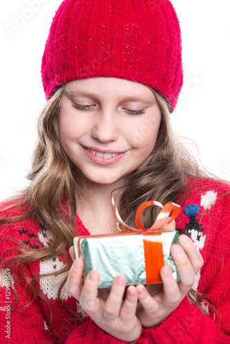 7ff38845839d Charming smiling little girl with curly hairstyle wearing red knitted  sweater and hat holding christmas gift isolated on white background.