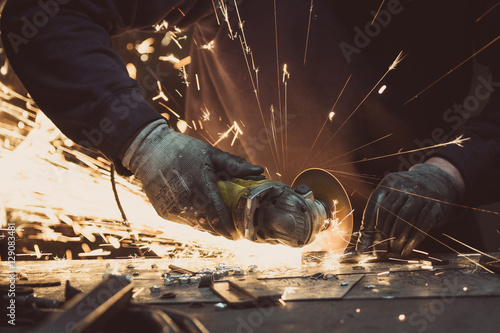 Fotografie, Obraz  Man sawing metal with a rotary angle grinder on an aluminium surface and generat