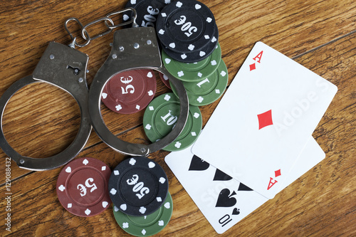 Illegal gambling concept blackjack with betting chips and handcuffs плакат