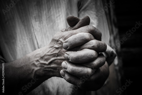 A man holds his hands in front of him. Fingers intertwined. Wallpaper Mural