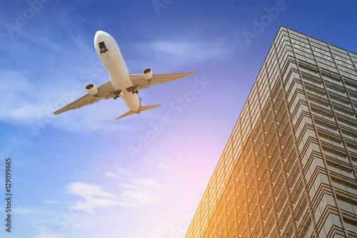 Airplane flying over building tower and sunny Wallpaper Mural