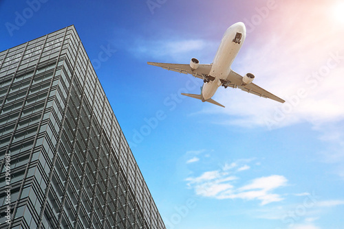 Airplane flying over building tower and sunny Canvas Print