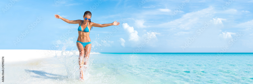 Fototapeta Sexy bikini body woman playful on paradise tropical beach having fun playing splashing water in freedom with open arms. Beautiful fit body girl on travel vacation. Banner crop for copyspace.