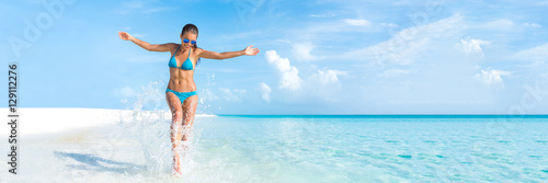 Fototapeta Sexy bikini body woman playful on paradise tropical beach having fun playing splashing water in freedom with open arms. Beautiful fit body girl on travel vacation. Banner crop for copyspace. obraz